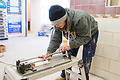 Tiling student using the tile cutter, Able Skills, Dartford, Kent.