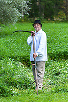Farmer standing with scythe in meadow. Traditional agricultural work, Estonia.