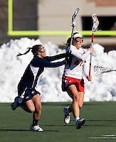 Brittany Poist (27) of Maryland is poke checked by Kara Moschetti (2) of Richmond at the practice turf field in College Park, Maryland.  Maryland defeated Richmond, 17-7.