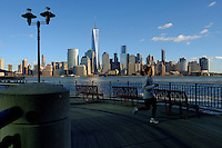 The World Trade Center and New York's lower Manhattan are seen at the background while a woman jogs on a boardwalk during a sunny day in the Neighborhood of Exchange Place in New Jersey, 12/15/2015 Photo by VIEWpress