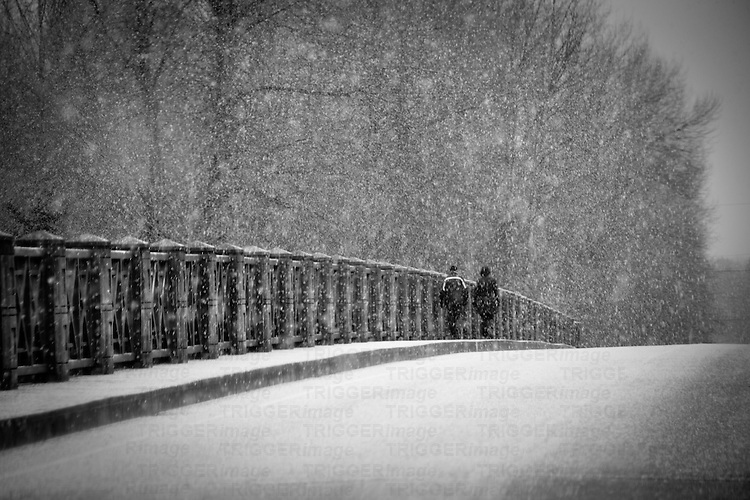 Two people walking across bridge through a snow storm.