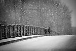 Two people walking across bridge through a snow storm.