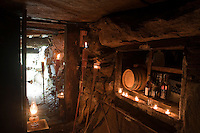 The interior of the root cellar which was excavated amongst huge boulders is lit with candles and paraffin lamps and is used as a larder in winter time