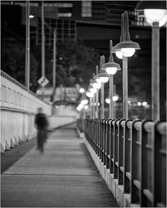 An early morning bicycler commutes over the First Street Bridge in Austin, Texas. Below are the cold waters of Ladybird Lake.
