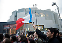 A man waves a flag in front of L'opera Bastille