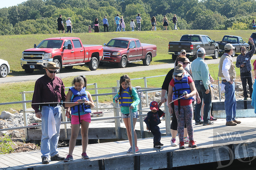NWA Democrat-Gazette/FLIP PUTTHOFF <br /> Ron Blackwelder (left) with the Bella Vista Fly Tyers helps students fish while other R.E. Bakers students walk to another station during a nature education day Sept. 30 2016 at Lake Windsor in Bella Vista.
