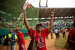 A fan waves her arms in the air after Santiago de Cuba won game two of the National Series against Pinar del Rio, on Sunday, April 20, 2008...When music and dancing are the rhythm and soul of life on this island nation, baseball is the passion. It gives Cubans something to dance to and something to cheer for when there's little else. It's what makes them feel free of government politics...Baseball is everywhere – in the streets, on TV, or empty fields. It's in conversation over peso pizza or debates in the Central Plaza. .