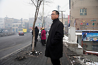 Han Chinese wait at a bus stop in Urumqi, Xinjiang, China. The city is divided between Han and Uighur ethnicities, and violent clashes erupted between the groups in 2009.