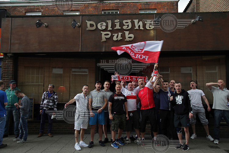 Polish football fans outside a pub where they are watching their national team playing in the Euro 2016 tournament. Along with the Polish flag, scarves and replica kit is a man wearing an umtra-nationalist 'Antykomuna' t-shirt. <br /> The town of Boston had the country's highest proportion of 'leave' votes cast in the EU referendum with almost 76 percent of ballots cast for Brexit. Lincolnshire has, in recent years, seen an influx of EU workers drawn to the area's agricultural industry. The 2011 census found about 13 percent of Boston's residents were born in Eastern Europe and migrated to the UK since 2004.