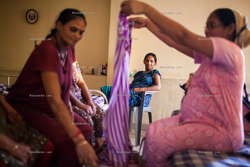 Surrogates try out 2nd hand maternity dresses when a salesman brings them to the surrogates hostel on the 3rd floor of Dr. Nayana Patel's Akanksha IVF and surrogacy center in Anand, Gujarat, India on 10th December 2012. Photo by Suzanne Lee / Marie-Claire France