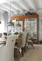 """The large kitchen table is described by the owners as the """"nerve-centre"""" of the house and is surrounded by a mixture of cane and upholstered dining chairs"""