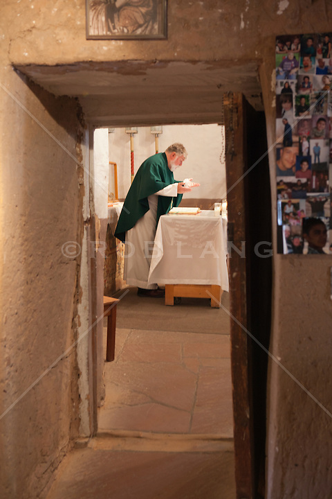 priest at the alter of a church giving a sermon in an adobe church