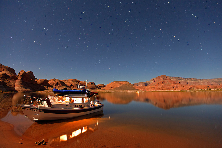Beneath a starry night sky, a boat rests in Oak Canyon on Lake Powell within the Glen Canyon National Recreation Area, Utah, USA (Model release available)