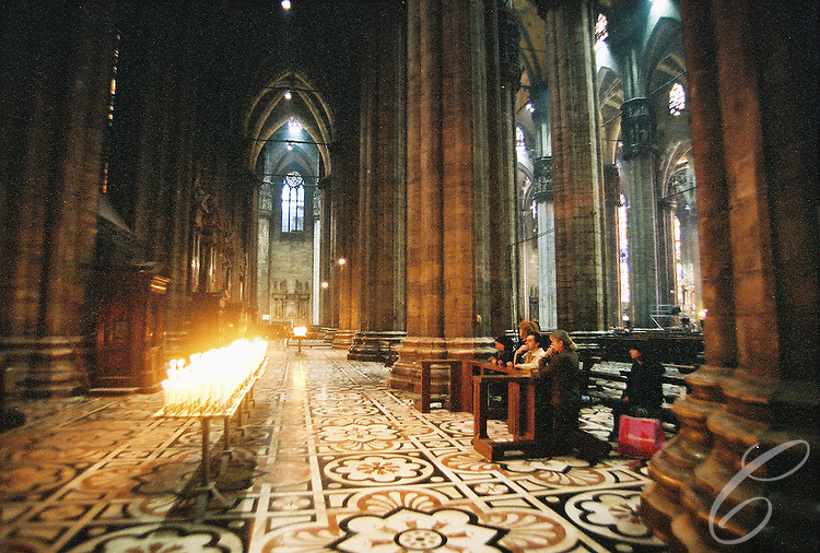 Worshipers pray in the Duomo in Milan Italy in March of 2004.