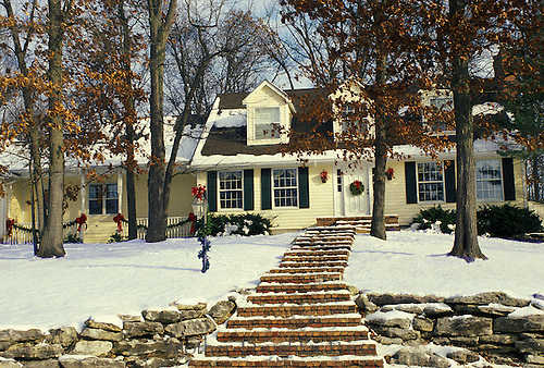 Yellow Cape cod style house decorated for Christmas