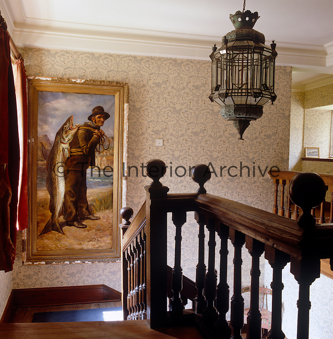 A gilt-framed painting of a fisherman is displayed on the staircase landing against a wallpaper with a delicate floral motif