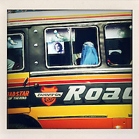 A woman in a burqa sits next to the open window of a passenger coach.