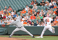 Casey Kotchman #13 of the Seattle Mariners can't stop Adam Jones #10 of the Baltimore Orioles getting on first base during a MLB game at Camden Yards, on August 8 2010, in Baltimore, Maryland. Orioles won 5-4 in extra innings.
