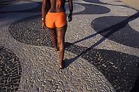 View from behind of sensual young black woman walking at Copacabana pedestrian walkway ( calçadão de Copacabana ) wearing short  - Rio de Janeiro - Brazil.