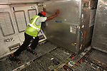Below economy class flooring, a cargo handler manhandles a container of freight in the hold of a Sri Lankan Airlines Airbus A340