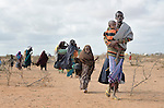 "Newly arrived refugees carry their belongings through the Dadaab camp in northeastern Kenya in 2011. Long the world's world's largest refugee settlement, Dadaab swelled with tens of thousands of new arrivals fleeing drought in Somalia. Under ""informed consent"" rules that require prior approval, the photographer would have had to stop the tired family, explain the intricacies of usage and consent, then get their signatures on the paperwork before allowing them to continue their trek across the hot desert. Photo by Paul Jeffrey."