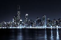 Photo of downtown Chicago city skyline at night with John Hancock Center building. The John Hancock Center is one of the world's tallest skyscrapers and is a famous fixture in the Chicago skyline. Photo is high resolution, toned blue and was taken in 2012.