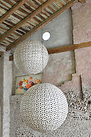 A rustic style living room with a pitched beamed roof and exposed stone walls. Two large paper globe lights hang from the ceiling.