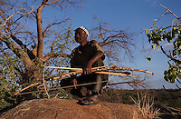 Yaeda Valley, Tanzania: Gonga Gonga, a Hadzabe man, at his lookout post in the hills surrounding this valley in Northern Tanzania. The Hadzabe are one of the last remaining tribes of hunter gatherers on earth. They are non-confrontational people, preferring to deal with conflict by running away deeper into the bush. The Hadzabe are under severe pressure from encroaching pastoral tribes, who bring cattle, disease and competition for water and grazing land that wild animals need. As a result, the number of wild zebras, elephants, antelope and other game have severely decreased. Hunters such as Gonga, who once killed four animals in a single day, can now go weeks without a catch. (PHOTO: MIGUEL JUAREZ LUGO).