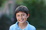 Young smiling boy outside in front of leafy tree background