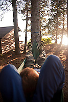 A man relaxes in a hammock at a backcountry campsite at Isle Royale National Park in Michigan USA.