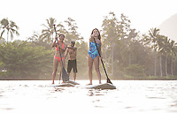 A family has fun learning how to standup paddle on Wailua River, Kaua'i.