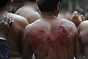 A man with gaping wounds watches other men hit themselves with ceremonial knives during Ashura. Ashura commemorates a day of mourning for the death of Hussein ibn Ali, the grandson of the Prophet Muhammad, at the battle of Karbala.  Shias consider Hussein the third Imam and the rightful successor to Muhammad. The grief for his death is demonstrated by the self-flagellation.  Lahore, Pakistan 2009