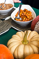 Cubed, roasted squash in a white bowl behind large orange and golden whole raw squash.