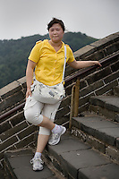 Zhangyang, a manager, age 25, poses for a portrait in Badaling. Response to 'What does China mean to you?': 'Home country.'  Response to 'What is your role in China's future?': 'Ordinary contribution.'