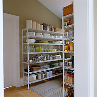 The pantry is lined with simple wire Metro shelving holding a variety of pots, pans and provisions