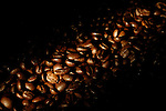 Arabica whole coffee beans shining with gold under artistic lighting Dark brown coffee bean background