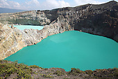 Colorful crater lakes on Kelimutu Volcano, Flores Island, Indonesia. The two lakes are highly acidic due to underwater fumarole activity and are turquoise in color.