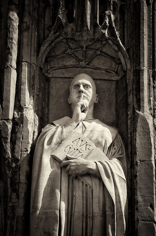 Stone statue of male figure holding open book with a finger to his lips indicating silence on Norwich cathedral