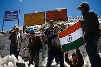 Tourists hold up the national flag of India for photos as they stop on the top of the Khardung La (Pass) at 5602m in the Nubra Valley, Ladakh on 4th June 2009. The valley of Ladakh is located in the Indian Himalayas, in the northern state of Jammu and Kashmir. Photo by Suzanne Lee
