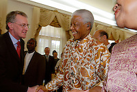 Former South African president Nelson Mandela (C) meets British Secretary of State for International Development Hilary Benn (L) at the presidential palace in Maputo after talks on education in Africa.