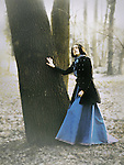 A brunette in a long blue dress and a black coat, standing by a huge tree, with eyes closed and an emotive expression.