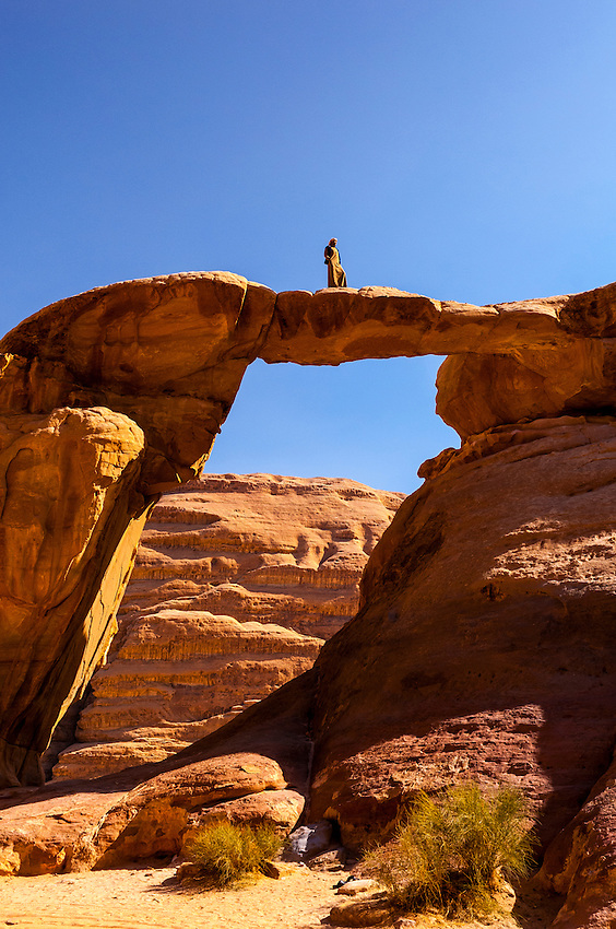 A Bedouin man atop the 100 foot tall (35 meters) Burdah Rock Bridge (an arch), Wadi Rum, in the Arabian Desert, Jordan.
