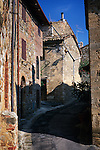 A shadow falls on a narrow alleyway road in an old Italian town