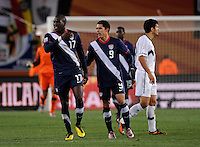 Jozy Altidore of USA shows his frustration as he is held back by Herculez Gomez