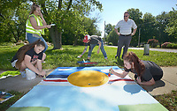 NWA Democrat-Gazette/BEN GOFF @NWABENGOFF<br /> Anya Bruhin (center), Pea Ridge Middle School art teacher, helps students from her 8th grade elective art class Sadie Prince (from left), Kailey King and Kyleigh Box paint their design Monday, May 15, 2017, as Pea Ridge Mayor Jackie Crabtree stops by to take a look, along Weston Street in front of the school in Pea Ridge. Students in the class partnered with UpStream Art to learn about water quality issues before working in small groups to designs and paint murals on six storm drains near the school.