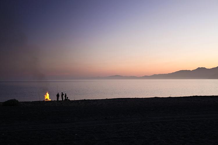 Dusk silhouette of fishermen on South Kaikoura beach with camp fire. New Zealand - stock photo, canvas, fine art print