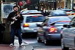 Guitarist on the sidewalk in front of Pioneer Square playing for the cars that are passing by.
