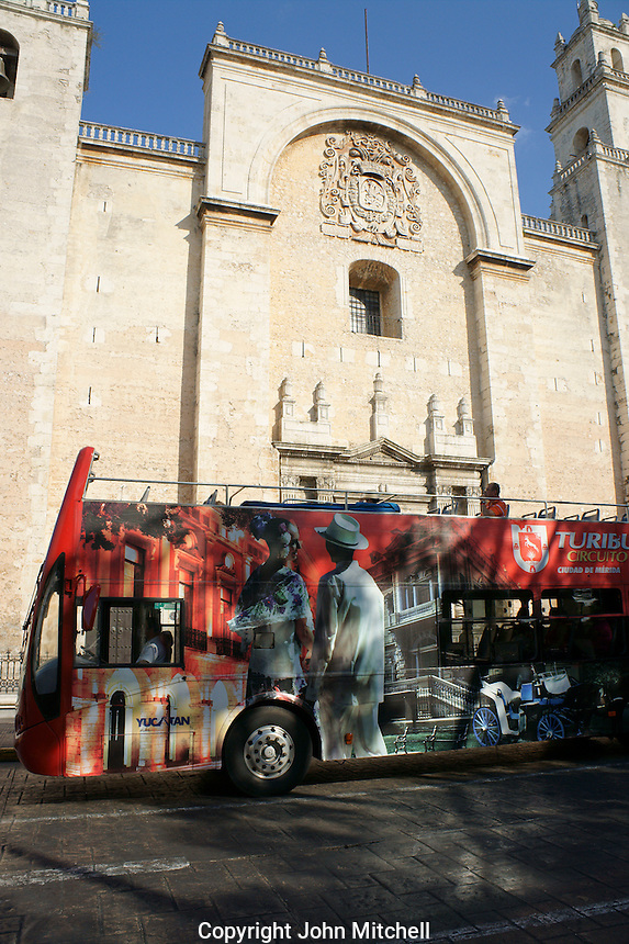 Colorful double decker open air tourist bus or turibus in front of the cathedral in Merida, Yucatan, Mexico.