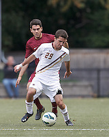 Boston College midfielder Brendan Hayes (29) dribbles as Harvard University defender Tyler Evans (3) defends.Boston College (white) defeated Harvard University (crimson), 3-2, at Newton Campus Field, on October 22, 2013.
