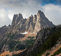 Early Winters Spires, North Cascades National Park, Washington, USA. The individual spires, left to right, are Lexington Tower, Concord Tower, and Liberty Bell. The granite spires are of the 45-million-year-old (Eocene) Golden Horn Batholith and were carved into the steep-sided cliffs by glaciers. The larger notches separating the towers are small faults.
